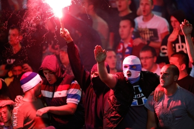 Serbian national football team supporters light a flare during the Euro 2016 Group I qualifying match between Serbia and Albania at the Partizan stadium in Belgrade, Serbia, Tuesday, Oct. 14, 2014. The European Championship qualifier between Serbia and Albania was suspended on Tuesday after pitch skirmishes involving players and fans over an Albanian flag banner that was flown above the stadium by a drone. (AP Photo/Marko Drobnjakovic)